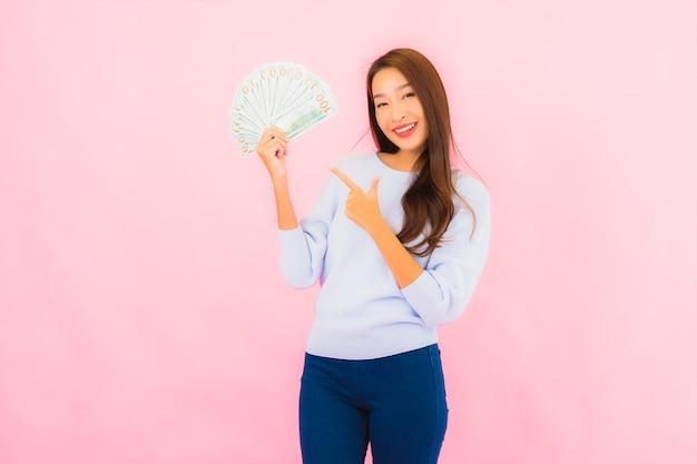 Ritratto bella giovane donna asiatica con un sacco di soldi e contanti sulla parete di colore rosa