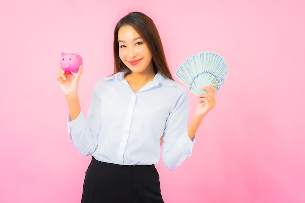 Portrait beautiful young asian woman with a lot of cash and money on pink wall