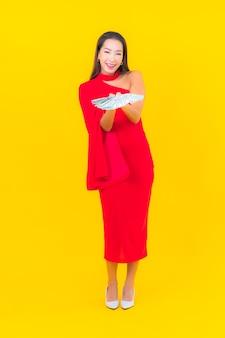 Bella giovane donna asiatica del ritratto con molti contanti e soldi