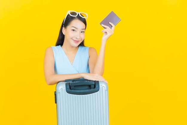 旅行の準備ができて荷物バッグとパスポートを持つ肖像画の美しい若いアジアの女性