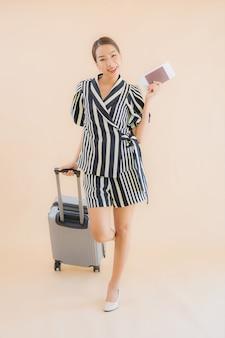 荷物バッグのパスポートを持つ美しい若いアジア女性の肖像画