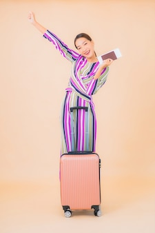 色で旅行の準備ができて荷物パスポートと搭乗券を持つ肖像画の美しい若いアジアの女性