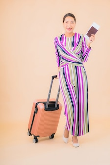 Portrait beautiful young asian woman with luggage passport and boarding pass ready for travel on color