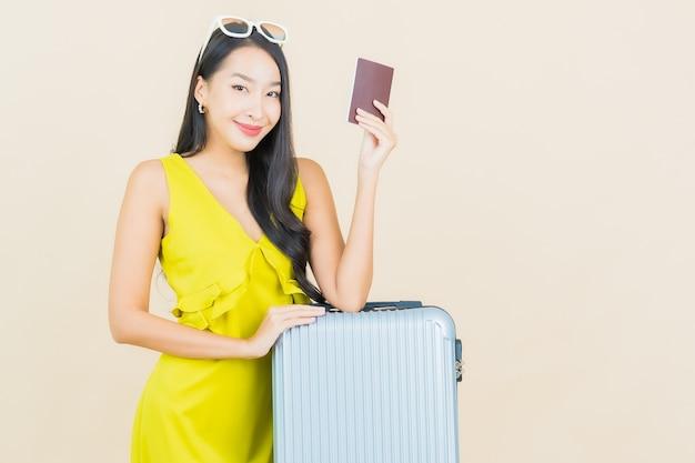 色の壁で旅行の準備ができて荷物パスポートを持つ肖像画の美しい若いアジアの女性