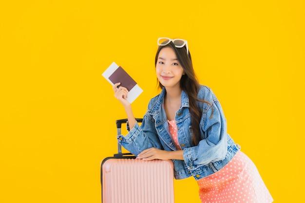 Bella giovane donna asiatica del ritratto con la borsa di viaggio dei bagagli con il biglietto del passaporto e di imbarco
