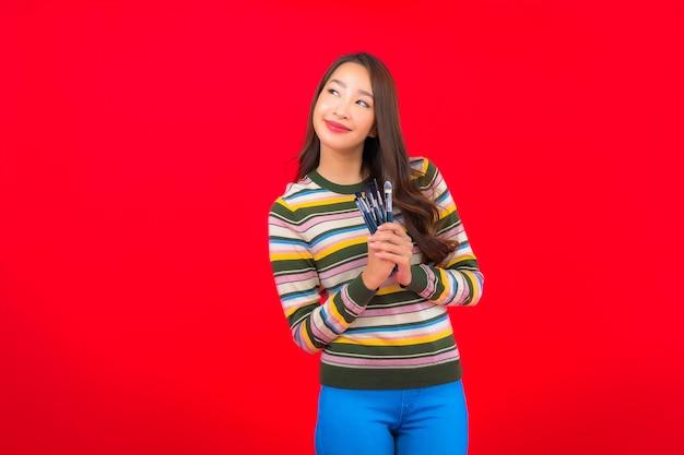 붉은 벽에 메이크업 브러시와 화장품 초상화 아름 다운 젊은 아시아 여자