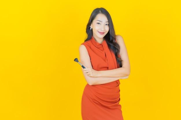 노란색에 메이크업 브러쉬 화장품을 가진 아름다운 젊은 아시아 여성의 초상화