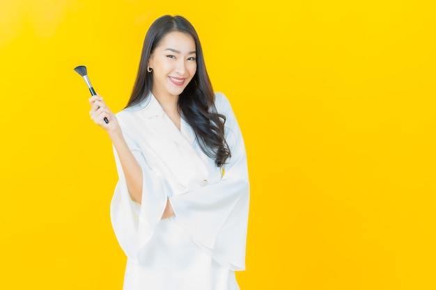 Portrait of beautiful young asian woman with make up brush cosmetic on yellow wall