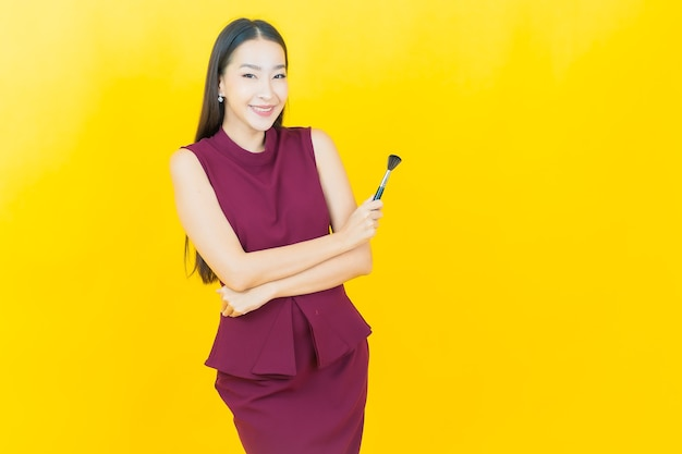Bella giovane donna asiatica del ritratto con il cosmetico della spazzola di trucco sulla parete gialla