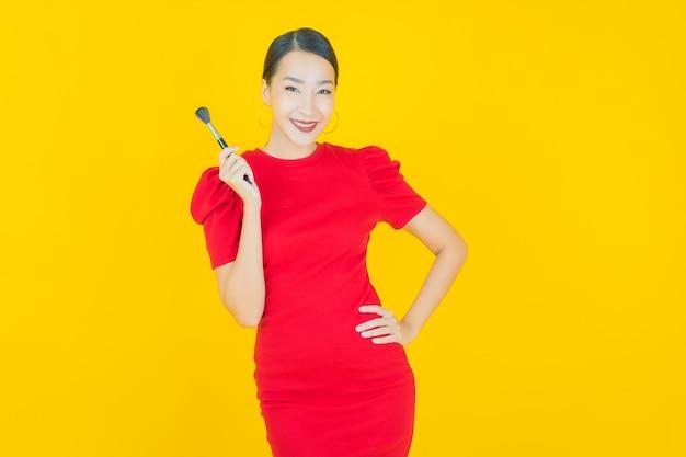 Bella giovane donna asiatica del ritratto con il cosmetico della spazzola di trucco su yellow