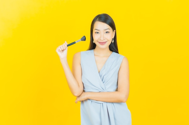 Женщина портрета красивая молодая азиатская с косметикой кисти