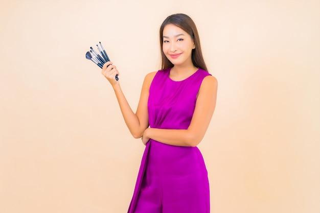 격리 된 색상 배경에 메이크업 브러시와 초상화 아름 다운 젊은 아시아 여자