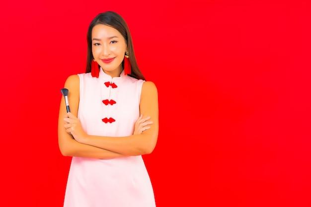 La bella giovane donna asiatica del ritratto con compone la spazzola cosmetica sulla parete isolata rossa