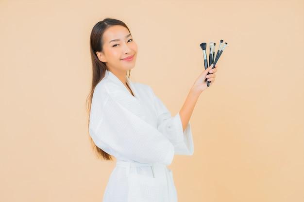 ベージュの化粧ブラシと肖像画の美しい若いアジアの女性