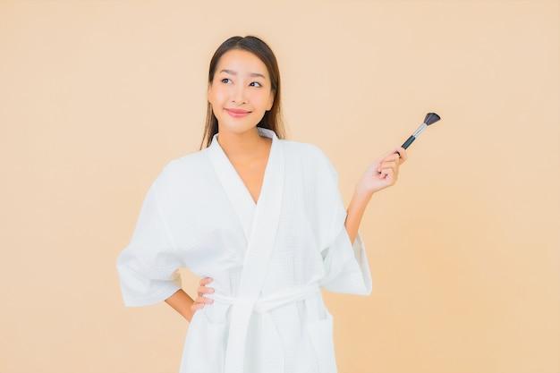 베이지 색에 메이크업 브러시와 세로 아름 다운 젊은 아시아 여자