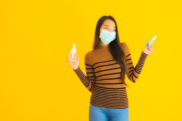 Женщина портрета красивая молодая азиатская с брызгом спирта маски и бутылкой геля в ее руке для защищает от coronavirus или covid19