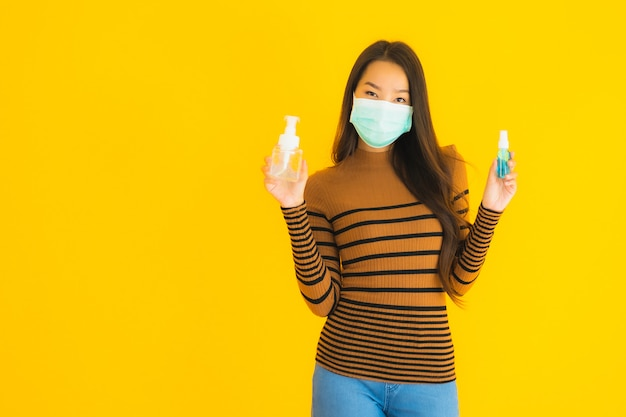 Portrait beautiful young asian woman with mask alcohol spray and gel bottle in her hand for protect from coronavirus or covid19