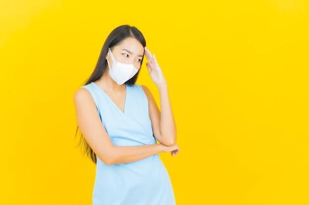 黄色の色の壁にcovid19またはウイルスを保護するためのマスクを持つ肖像画の美しい若いアジアの女性