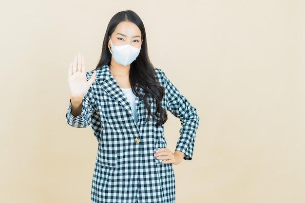 Covid19または黄色のウイルスを保護するためのマスクを持つ美しい若いアジア女性のポートレート