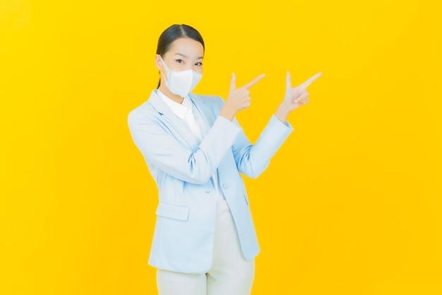 Covid19または黄色のウイルスを保護するためのマスクを持つ肖像画の美しい若いアジアの女性