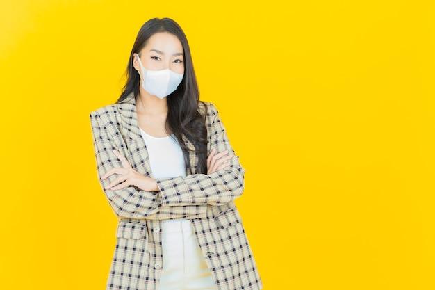Covid19またはウイルスを保護するためのマスクを持つ肖像画の美しい若いアジアの女性