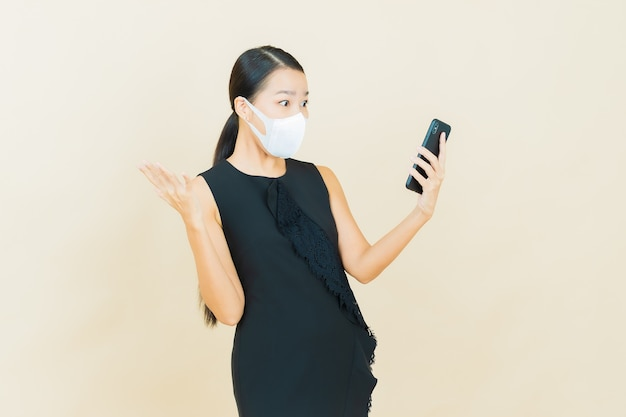 Portrait beautiful young asian woman with mask for protect covid19 or virus on yellow color wall