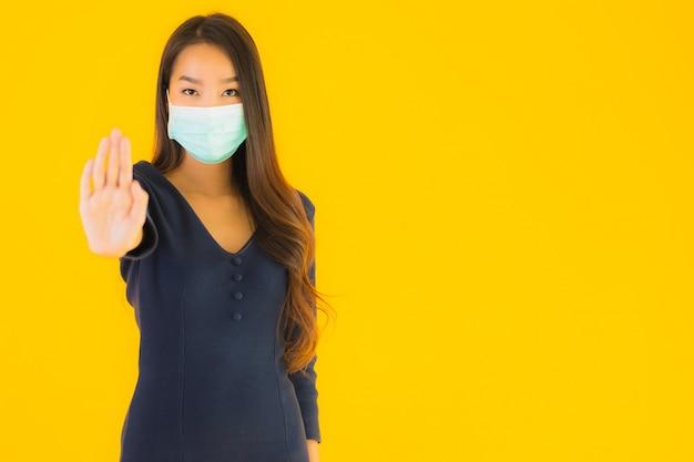 肖像画のマスクを持つ美しい若いアジア女性