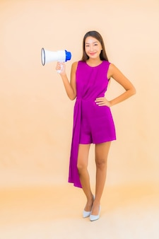 Portrait beautiful young asian woman with megaphone on color isolated background