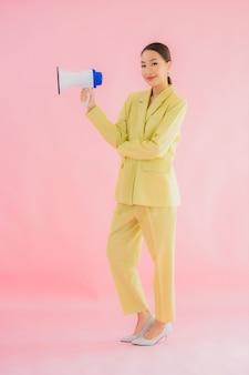 Bella giovane donna asiatica del ritratto con il megafono sul colore