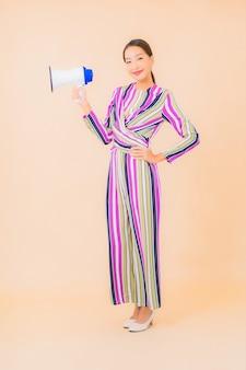 Bella giovane donna asiatica del ritratto con il megafono per la comunicazione sul colore