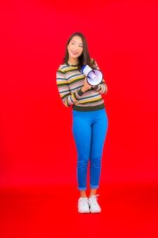 Bella giovane donna asiatica del ritratto con il megafono per la comunicazione sulla parete rossa