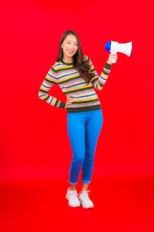 赤い壁の通信のためのメガホンと肖像画の美しい若いアジアの女性