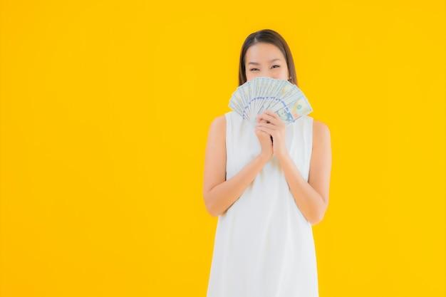 お金の現金を持つ美しい若いアジア女性の肖像画