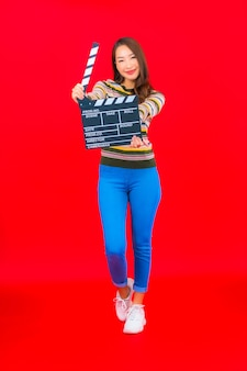 Portrait beautiful young asian woman with movie slate cutting on red isolated wall