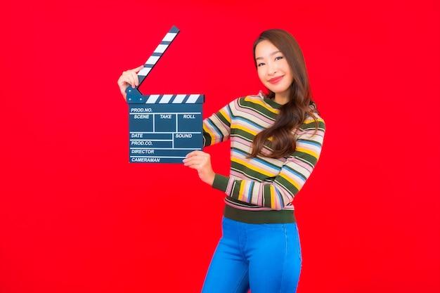 Bella giovane donna asiatica del ritratto con il taglio dell'ardesia di film sulla parete isolata rossa