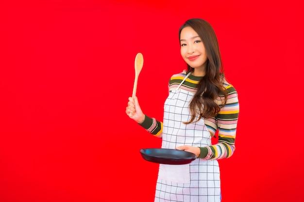 Ritratto bella giovane donna asiatica con padella pronta da cucinare sulla parete rossa