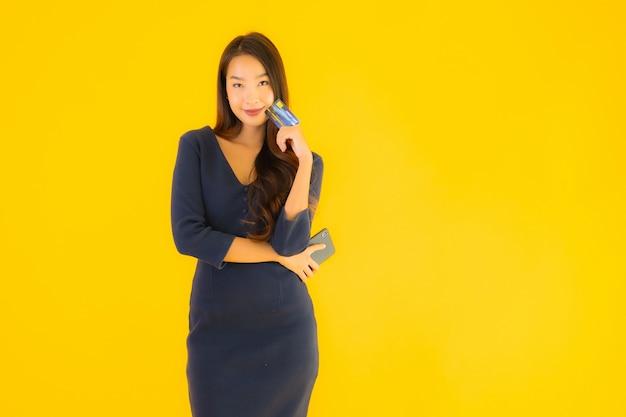 Женщина портрета красивая молодая азиатская с телефоном и кредитной карточкой