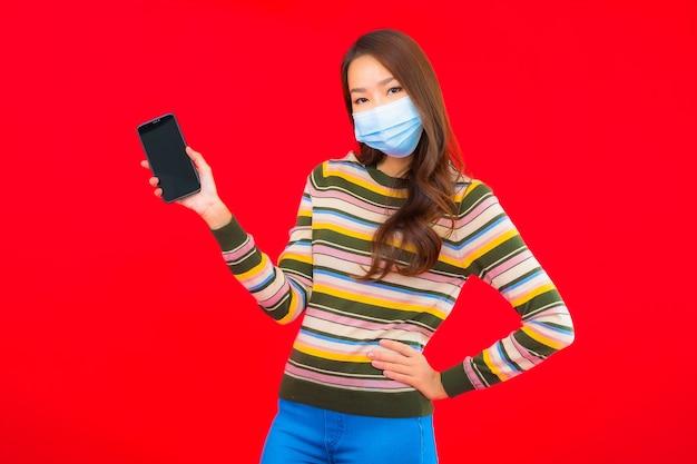 Covid19を保護するための電話着用マスクを持つ肖像画の美しい若いアジアの女性