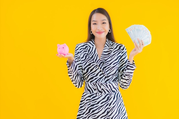 Портрет красивая молодая азиатская женщина с копилкой и наличными или деньгами на желтом