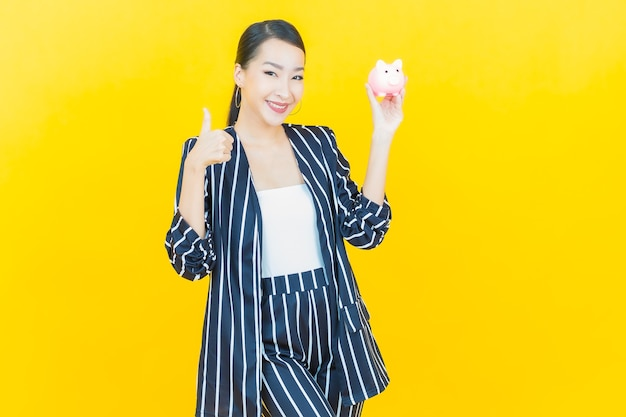 Portrait beautiful young asian woman with piggy bank on color background
