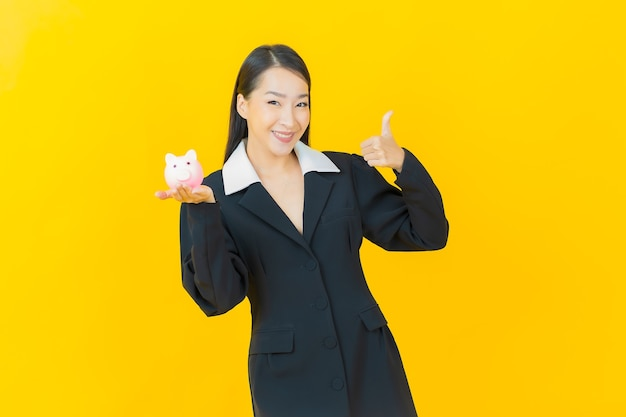 Portrait beautiful young asian woman with piggy bank on color wall