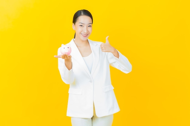 色の壁に貯金箱を持つ肖像画の美しい若いアジアの女性