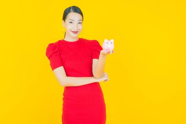 黄色の貯金箱と肖像画の美しい若いアジアの女性