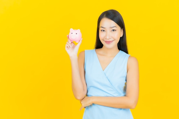 Portrait beautiful young asian woman with piggy bank on yellow color wall