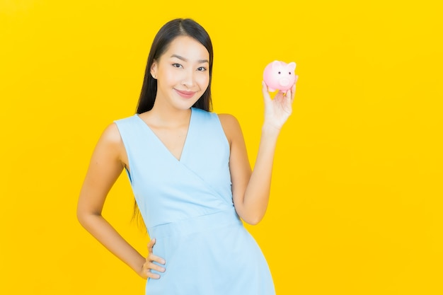 Ritratto bella giovane donna asiatica con salvadanaio sulla parete di colore giallo