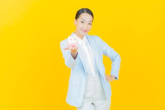 Ritratto bella giovane donna asiatica con salvadanaio su yellow