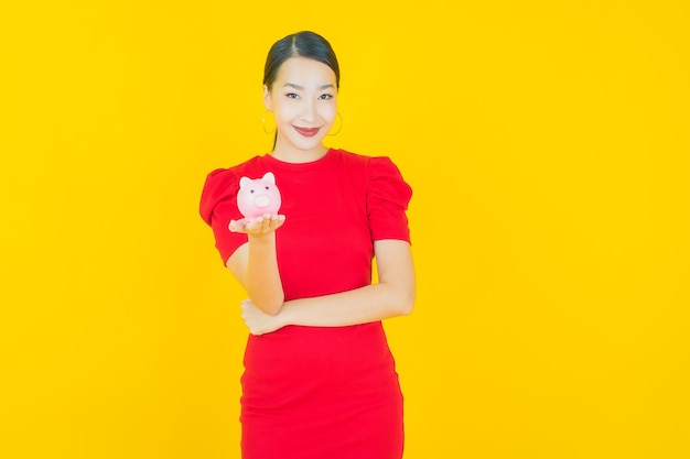 Portrait beautiful young asian woman with piggy bank on yellow