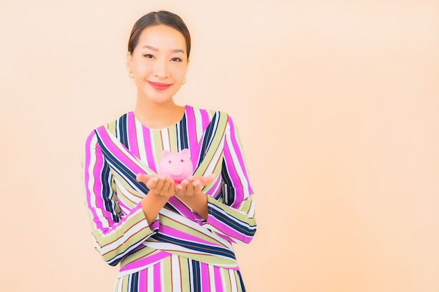 Portrait beautiful young asian woman with pink piggy bank on color