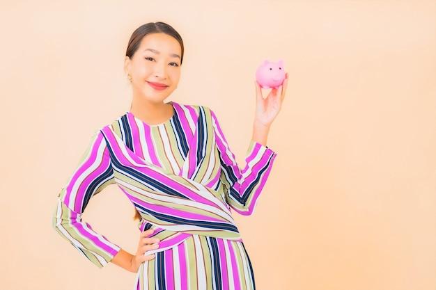 Bella giovane donna asiatica del ritratto con il porcellino salvadanaio rosa sul colore