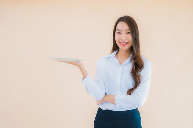 Bella giovane donna asiatica del ritratto con il piatto o il piatto